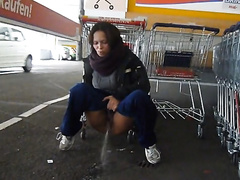 German girl pisses in the cart parking area at a store