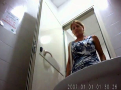 Blonde milf in a blue dress uses public toilet