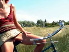 Redhead sits on a bike and pisses outdoors