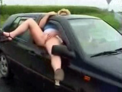Curvy woman pisses out the window of driving car