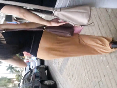 Slim charming lady walks around in a skirt that accentuates her firm buttocks