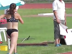 Athletic girl runs around the track in tight clothes