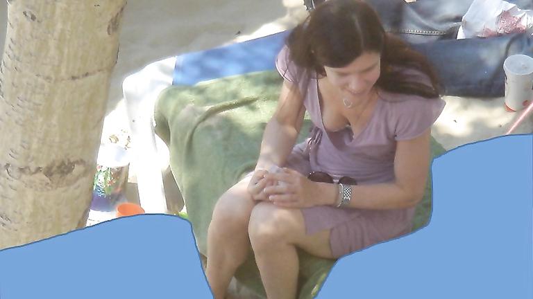 Irresistible gals enjoy sunbathing at a sandy beach