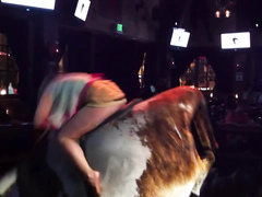 Blonde with long legs tries to ride on the bull