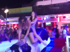 Two sexy chicks jumps on an mechanical bull while being topless