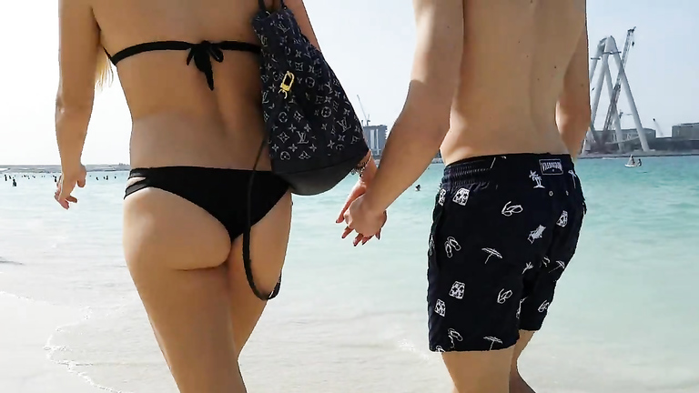 Girlfriend in a tight bikini strolls down the beach with her boy