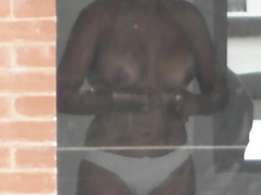 Busty woman filmed in secret while naked next to the window