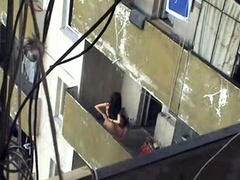 Girl sits on his balls out on the balcony
