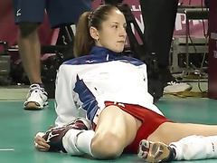 Volleyball girl in skintight shorts stretches before match