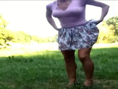My playful spouse in a short skirt piddles in the grass