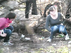 Two college girls squat and pee in the woods