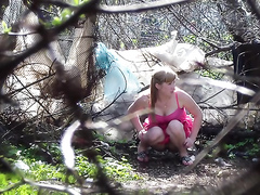 Busty damsel dressed in pink takes a leak in the open air