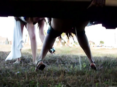 Girl pissing against a car in a grassy field