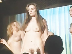 Naked beauties dance on stage for an audience of men