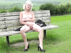 Naked British mature sits on a park bench