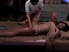 Horny masseuse fingers a beautiful Asian client to orgasm
