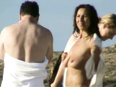 Naked ladies at the beach dry off after a swim