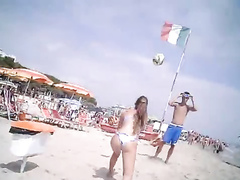 Bikini girl and her man play with a volleyball